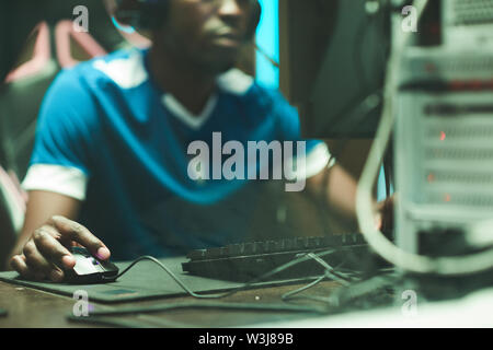 Close-up of black man in tshirt sitting at table with cables and clicking with mouse while shooting in computer game - Stock Image