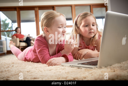 Two little girls with laptop at home - Stock Image