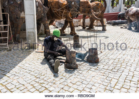 an artist is welding together the sections of recycled metal being used to form an elephant, part of the African art section of Quinta dos Loridos - Stock Image