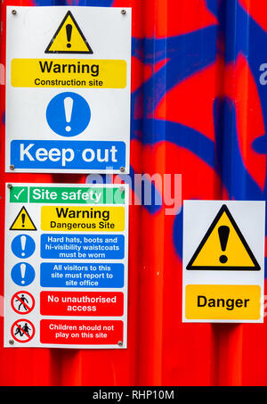 Danger and warning signs mounted on a metal conatiner with graffiti Liverpool January 2019 - Stock Image