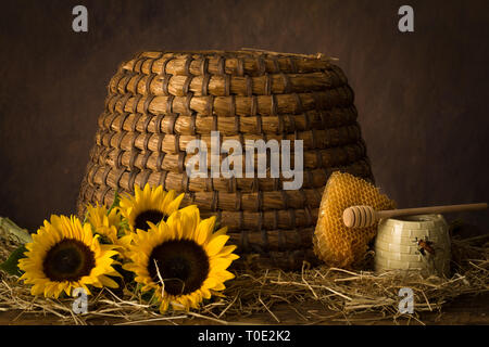 Sunflowers with honeycomb and honey pot in front of an antique beehive - Stock Image