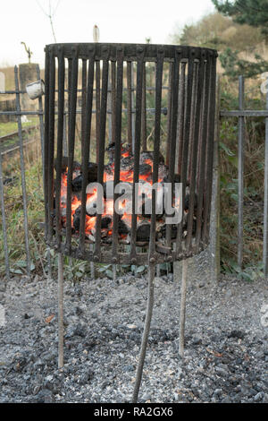 A coal fire within a riveted steel brazier, Beamish Museum, north east England, UK - Stock Image