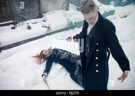 Duel of dark and light magicians with the help of magic wands on the snow background. - Stock Image