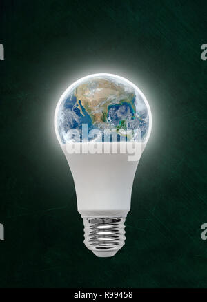 Illuminated energy efficient Light Emitting Diode LED light bulb with planet earth inside. Concept of ecology, environmental conservation; green alter - Stock Image