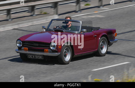A classic Triumph TR6 drives along the road - Stock Image