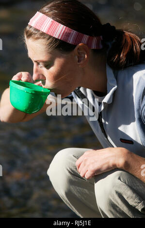 Woman drinking out of a cup - Stock Image
