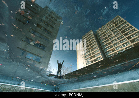 water reflection,puddle,tenement block - Stock Image