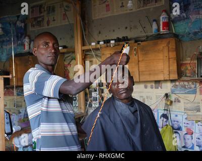 TANZANIA  -  photo by Sean Sprague 2018  Bukundi, Shinyanga. Street scene. Barber, - Stock Image
