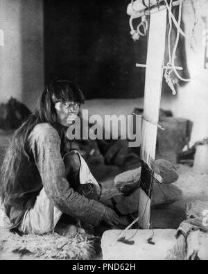 1890s 1898 NATIVE AMERICAN INDIAN MAN LOOKING AT CAMERA WEAVING CEREMONIAL KILT ON LOOM  - q73416 CPC001 HARS PRECISION WEAVE WEAVING YOUNG ADULT MAN BANGS BLACK AND WHITE CEREMONIAL KILT LOOM OLD FASHIONED WEAVER - Stock Image