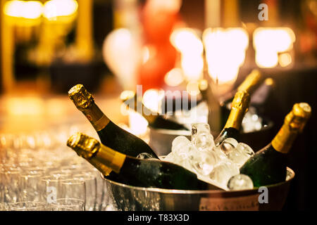 Night event party celebration concept with fluts glasses and wine champagne bottles ready to be drinked from people - bokeh defoused light background - Stock Image