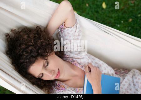 young woman lying in hammock in garden sleeping - Stock Image