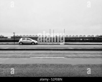 A single car parked on a deserted Kingsway in front of beach huts by the Hove waterfront, East Sussex, on a grey and dull Sunday. - Stock Image