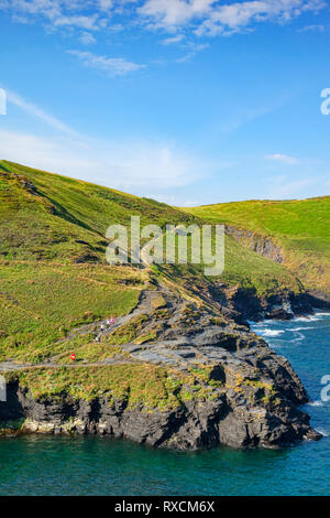 2 July 2018: Boscastle, Cornwall, UK - The South West Coast Path on the cliff tops near Boscastle, as a group of people walk down toward the harbour. - Stock Image