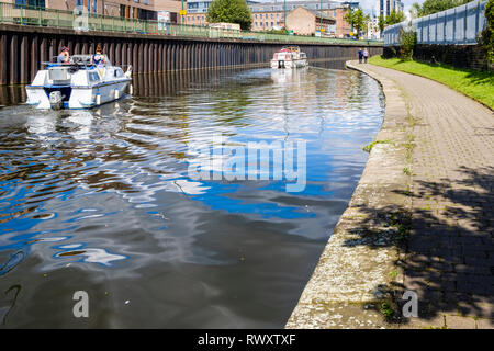 Boats sailing on a city canal and people walking on the towpath, Nottingham And Beeston Canal at Nottingham, England, UK - Stock Image