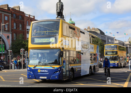 Double decker buses passing the Daniel O'Connell Monument in O'Connell Street, Dublin, County Dublin, Republic of Ireland, Eire - Stock Image