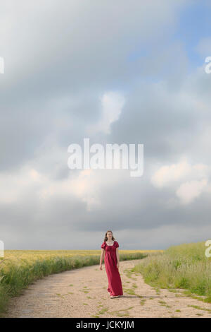 a woman in a red dress is walking on a path through grainfields - Stock Image