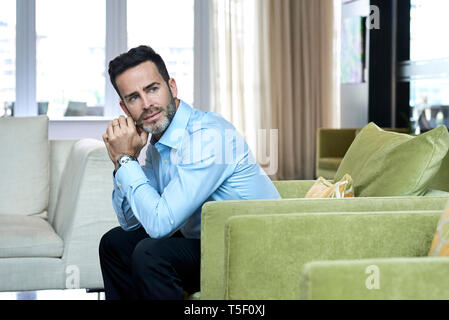 Thoughtful businessman sitting in hotel lobby - Stock Image