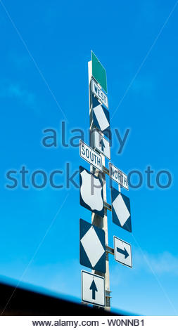 Highway direction signs with arrows to North, South, and West, and three blank diamonds, one blank shield, one blank square. - Stock Image