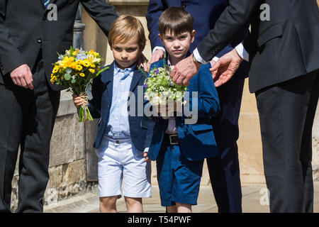 Windsor, UK. 21st April 2019. Two young boys arrive to give traditional posies of flowers to the Queen as she leaves the Easter Sunday service at St George's Chapel in Windsor Castle. Credit: Mark Kerrison/Alamy Live News - Stock Image