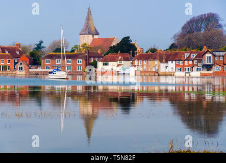 Picturesque old village houses reflected in still waters of Bosham Creek at high tide in Chichester harbour. Bosham, West Sussex, England, UK, Britain - Stock Image