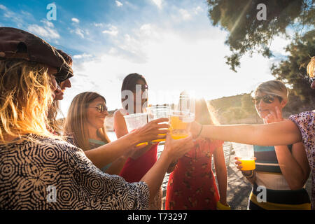 Group of people young pretty women girls toasting and clinking together outdoor during sunset sunlight having fun for friendship - summer party vacati - Stock Image