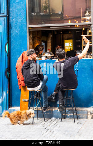 Two young men and a dog outside a bar in Seville - Stock Image