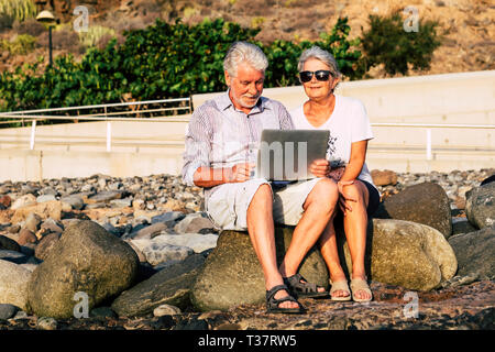 adult senior aged couple cacuasian people use technology laptop computer outdoor in a sunny day - internet everywhere and retired man and woman with n - Stock Image