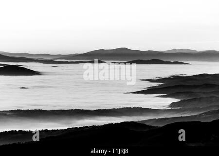 Fog filling a valley in Umbria (Italy), with layers of mountains and hills - Stock Image