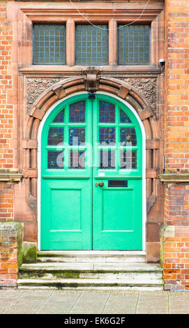 A green double arched door in a red brick building in the UK - Stock Image