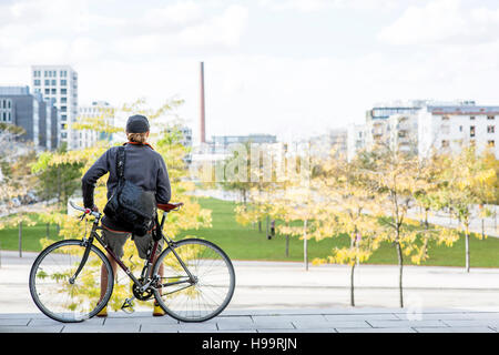 Bike messenger looking over city - Stock Image