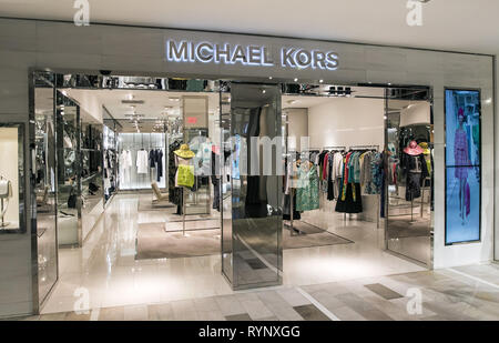 New York, 3/11/2019: Dresses and other clothing items hang at the Michael Kors section at Bloomingdale's department store in Manhattan awaiting attent - Stock Image