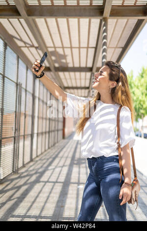 Portrait of a beautiful young woman selfie in the park with a smartphone - Stock Image