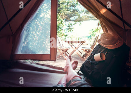 view of crossed feet of a hiker man resting barefoot in a camping tent, travel discovery concept, point of view shot - Stock Image
