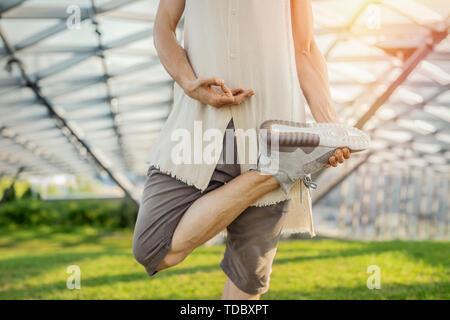 Close up of attractive athletic man practicing yoga and meditating in modern park at green grass outdoors. - Stock Image