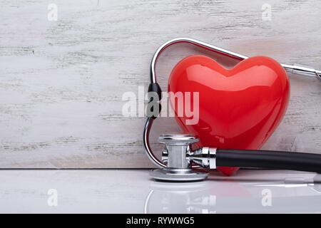 Close-up Of Stethoscope Around Shiny Red Heart On White Desk - Stock Image