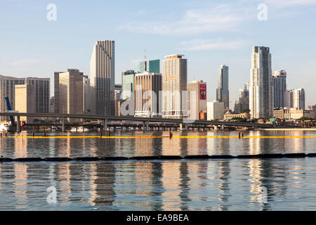 High-rises of the Miami skyline are reflected in the calm waters of Biscayne Bay in the early morning sunlight, - Stock Image