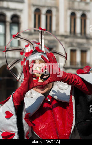 Venice, Italy. 25th Feb, 2014. A masked performer dressed in a Queen of Hearts costume makes the shape of a heart with her hands in San Marco. Venice Carnivale Credit:  MeonStock/Alamy Live News - Stock Image