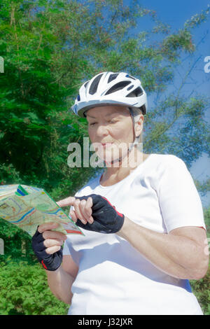 Senior woman outdoors in the summer sun with bicycle helmet, gloves, white t-shirt and map, getting a nice suntan - Stock Image