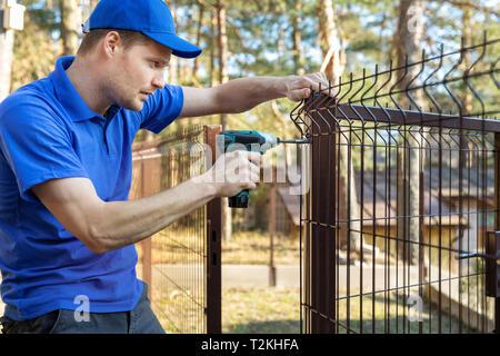 property territory fencing - man screws metal fence panel - Stock Image