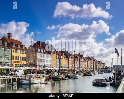 23 September 2018: Copenhagen, Denmark - The canal lined with boats and colourful houses  at Nyhavn on a sunny autumn say with big fluffy white clouds - Stock Image
