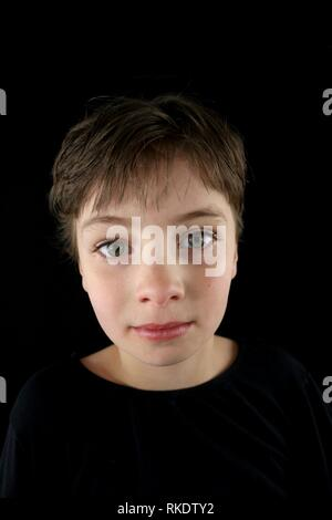 Portrait of a serious looking child with a pixie haircut against a black background - Stock Image