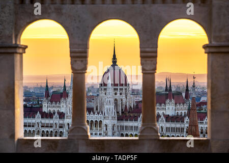 Budapest, Hungary - The Hungarian Parliament building at sunrise looking through old stone windows - Stock Image