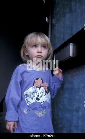 little blonde girl standing by open door looking suspiciously - Stock Image