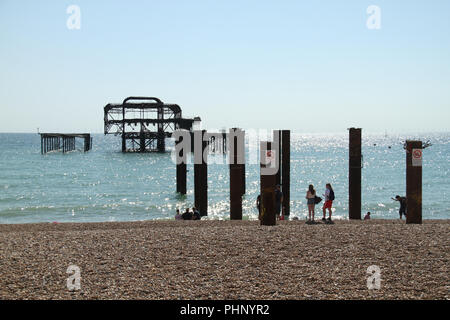 Brighton, UK - September 1 2018: People seen by the site of the West Pier in Brighton on a sunny afternoon of 1​ September 2018.  The  Pier was destroyed by fire in 2007 The Pier, in the central waterfront section, opened in 1899 houses amusment rides as well as food kiosks .Credit: David Mbiyu Credit: david mbiyu/Alamy Live News - Stock Image