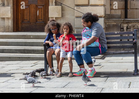 Woman sits watching over 2 girls eating icecream while pigeons peck around their feet in Kingston Parade by the Abbey in the city of Bath - Stock Image