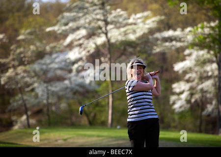 A woman tees off on the No. 7 hole at Branchwood Golf Course in Bella Vista, Ark., with dogwood trees in bloom behind - Stock Image