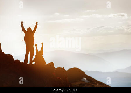 Silhouettes of two happy tourists at mountain top. Success or win concept - Stock Image