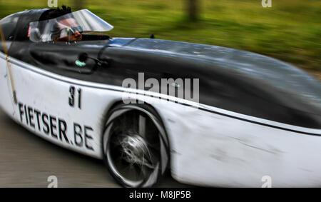 Streamlined aerodynamic bodywork on a recumbent trike pedal car speeding stabley around Richmond Park's roads - Stock Image