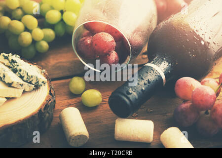 bottle of red wine with grapes and blue cheese - Stock Image