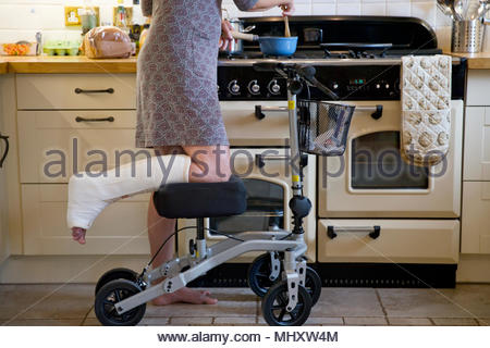 Close Up Of Woman With Leg In Plaster Cast At Home Using Mobility Aid Whilst Cooking Meal - Stock Image